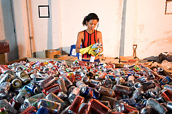 Mulher trabalhndo na reciclagem de latas de aluminio em cooperativa / Woman working in aluminium can recycling at one co-operative