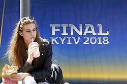 May 18, 2018 - Kiev, Ukraine - An Ukrainian woman sits near the logo the UEFA Champions League final in central Kiev, Ukraine, 18 May, 2018. The football UEFA Champions League final match between Real Madrid and Liverpool FC next May 26 at the NSC Olimpiyskiy Stadium. (Credit Image: © Str/NurPhoto via ZUMA Press)