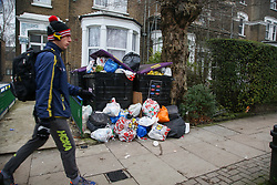 © Licensed to London News Pictures. 28/12/2020. London, UK. A man walks past bags of rubbish gathered in a front garden in north London after the festive period. Photo credit: Dinendra Haria/LNP