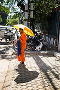 29 JUNE 2013 - PHNOM PENH, CAMBODIA:  A Buddhist monk on his morning alms rounds in a residential neighborhood in Phnom Penh, Cambodia.     PHOTO BY JACK KURTZ