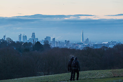 """Two walkers cross Hampstead Heath, with London's skyline in the distance. The threatened snow from """"The Beast From The East"""" weather system doesn't materialise overnight in London leaving a crisp, clear morning, seen from Hampstead Heath in North London. London, February 27 2018."""