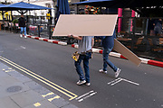 With their heads and faces obscured by their load, two workmen carry construction boards through Covent Garden in the West End, on 12th October 2021, in London, England.