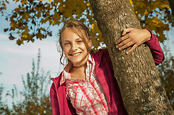 Girl holding tree trunk, smiling, portrait