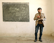 Teacher in front of black board at a government school . The traditional life of the Wakhi people, in the Wakhan corridor, amongst the Pamir mountains.