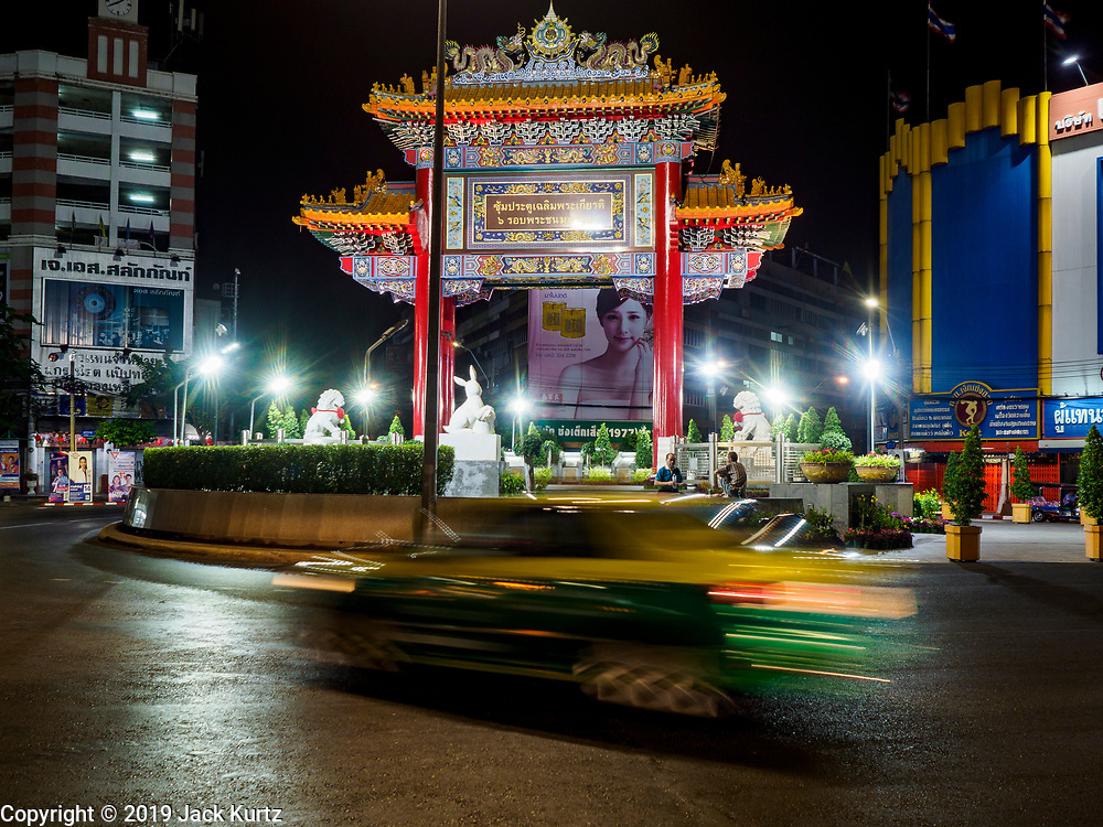 27 FEBRUARY 2019 - BANGKOK, THAILAND: A taxi goes around Odean Circle, the symbolic gate into Bangkok's Chinatown. Bangkok, a city of about 14 million, is famous for its raucous nightlife. But Bangkok's real nightlife is seen in its markets and street stalls, many of which are open through the night.       PHOTO BY JACK KURTZ