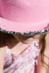 Little girl hiding under a hat,