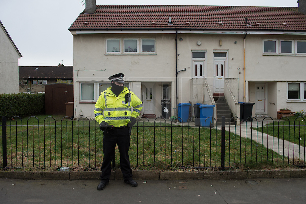 © Licensed to London News Pictures. 25/03/2016. <br /> <br /> Pictured: A police officer stands guard outside the home of John Leathem.<br /> <br /> Police Scotland have focused the centre of the murder investigation of 15 year old Paige Doherty in Clydebank, Glasgow around the home and business premises of suspect John Leathem as they search his house and Delicious Deli near Fleming Street, Clydebank Glasgow on Friday 25th March 2016.<br /> <br />  Photo credit should read Max Bryan/LNP