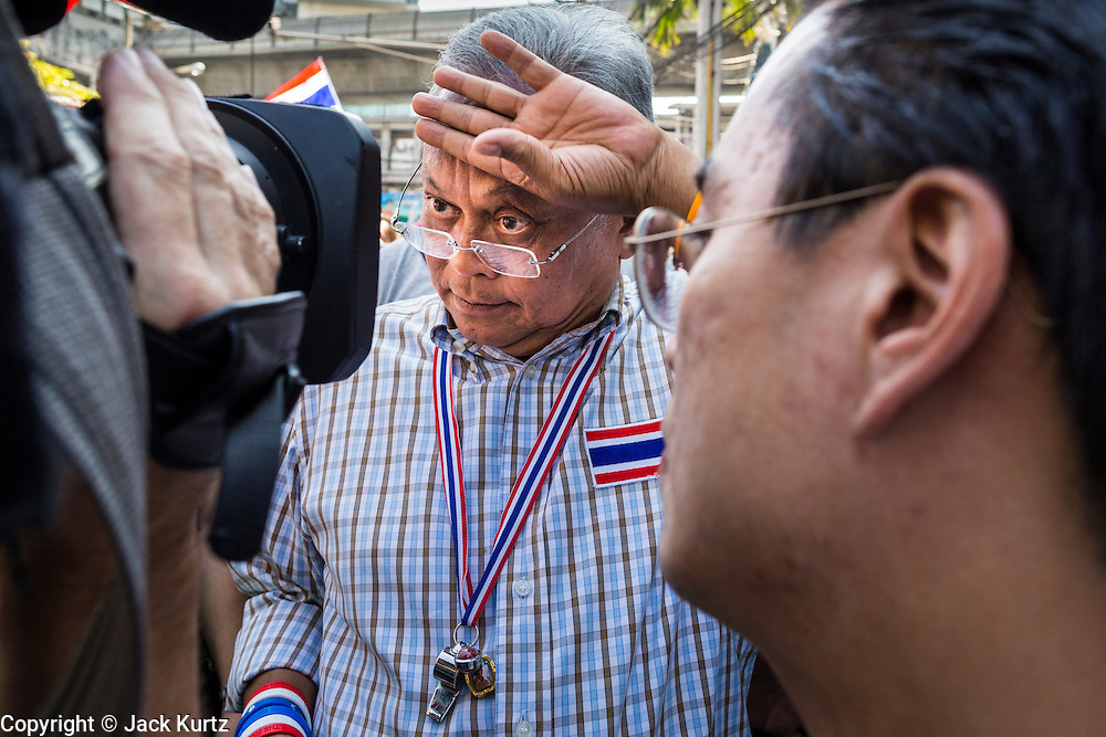 """15 JANUARY 2014 - BANGKOK, THAILAND:  SUTHEP THAUGSUBAN, former Deputy Prime Minister of Thailand and leader of the Shutdown Bangkok anti-government protests, wipes his brow while he gives an interview to a TV network during a protest march. Tens of thousands of Thai anti-government protestors continued to block the streets of Bangkok Wednesday to shut down the Thai capitol. The protest, """"Shutdown Bangkok,"""" is expected to last at least a week. Shutdown Bangkok is organized by People's Democratic Reform Committee (PRDC). It's a continuation of protests that started in early November. There have been shootings almost every night at different protests sites around Bangkok. The malls in Bangkok are still open but many other businesses are closed and mass transit is swamped with both protestors and people who had to use mass transit because the roads were blocked.   PHOTO BY JACK KURTZ"""