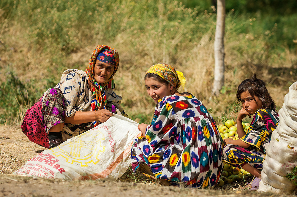 Portrait of a mother and daughters bagging their apple harvest in western Tajikistan
