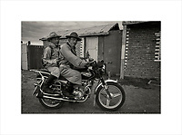 """Two Mongolian men on a Chinese made motorbike. Horses and Mongolians are virtually inseparable but a motorbike is also a prized possession. Note the sticker attached to the tank of the """"iron horse"""".<br /> Purchase a signed and numbered limited edition fine art print of this image from www.hanskemp.com/store"""