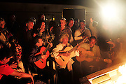 """Ricao Balliardo plays gitan music, surrounded by tourists, in his camping around the fire. Saintes Maries festival<br /><br />""""Le Pelerinage des Gitans""""; the French gypsy pilgrimage of Saintes Maries de la Mer, Camargue, France<br /><br />Sainte Sara is an uncannonized saint, who legend says looked after the Christian Saints Marie Jacobe and Marie Salome, cousins of Mary Magdalene, who arrived, it is said, on the shores of the Camargue in a rudderless boat. Saint Sara is the patron saint of gypsies who come from far and wide to see her. There are even paintings of Sara as 'Kali' the black saint in Eastern Europe. Sara may have been the priestess of 'Ra' the sun-god or even servant girl to the Christian saints. No-one really knows.<br /><br />For a few weeks of the year, Roma, Gitan and Manouche gypsies come from all over Europe in May, camping in caravans around Saintes Maries de la Mer. It is a festive time where they play music, dance, party and christen their children. They all go to see Saint Sara in the crypt, kissing or touching her forehead. Many put robes on her shoulders, making her fat for the procession. In the main Gypsy procession of the 24th May, Saint Sara is allowed to leave her crypt, beneath the church, and is carried from the church to the shores of the mediterranean and back again. One day a year she is free from her prison. Hundred's of years ago the Gypsies used not even to be allowed into the church, only into the crypt like Sara...<br /><br />Roma gypsies still suffer oppressive prejudice and racism and are one of the ethnic groups the most persecuted and marginalised across Europe. The festival is one of the times where they celebrate with people of all races, their faith and traditions"""