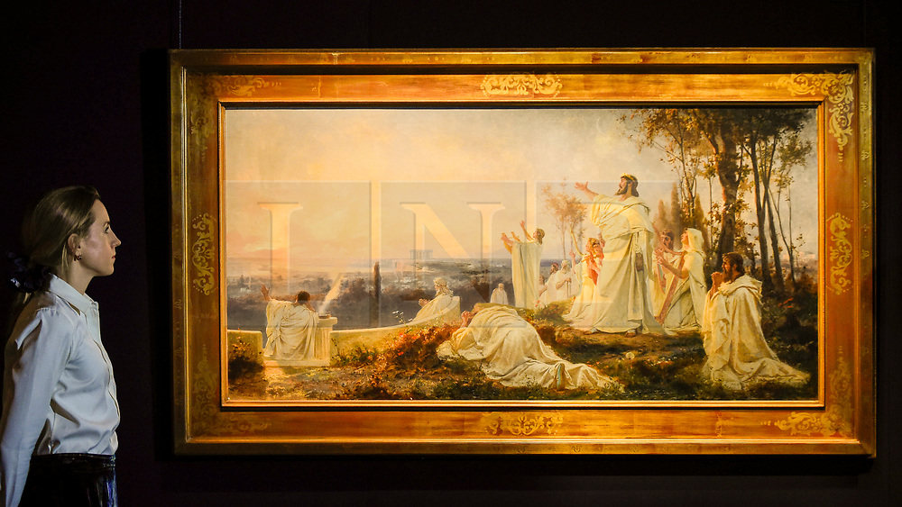 """© Licensed to London News Pictures. 22/11/2019. LONDON, UK. A staff member views """"Hymn of the Pythagoreans to the Rising Sun"""", 1877, by Fedor Bronnikov (Est. GBP300-500k) at the preview for the upcoming sales of Russian artworks at Sotheby's New Bond Street.  The Russian Pictures and Works of Art, Fabergé and Icons sales take place on 26 November.  Photo credit: Stephen Chung/LNP"""