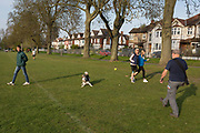 As the Easter Bank Holiday weekend begins and the UKs Coronavirus death toll rises to 7,978 with 65,077 cases testing positive by the end of the UK governments second week of lockdown, Londoners take their daily exercise with pet dogs while practicing social distancing in warm sunshine in Ruskin Park, a south London green space, on 9th April, in London, England.