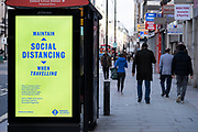 Transport for London digital advertising posters promoting social distancing at bus stops along Oxford Street which is empty of shoppers as the national coronavirus lockdown three continues on 28th January 2021 in London, United Kingdom. Following the surge in cases over the Winter including a new UK variant of Covid-19, this nationwide lockdown advises all citizens to follow the message to stay at home, protect the NHS and save lives.