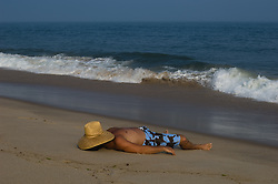 sexy man resting on the beach with a hat over his face in East Hampton, NY