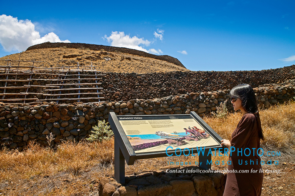 woman visitor looking at park sign at Puukohola Heiau - the temple on the whale hill, the largest and last heiau constructed in 1790-91 by Kamehameha I, Puukohola Heiau National Historic Site, Kawaihae, Kohala, Big Island, Hawaii, USA, Model Released - MR#: 000102, 000103