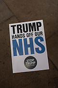 A Trump Hands Off Our NHS placard during the Stop Trump Coalition and CND protest against U.S. President Donald Trump UK visit to attend the NATO North Atlantic Treaty Organisation summit on the 3rd December 2019 in London in the United Kingdom. Ahead of a British national election on 12th December 2019, Stop Trump Coalition and CND, Campaign for Nuclear Disarmament organised a protest to target a banquet at Buckingham Palace where Trump will dine with the Queen and other NATO leaders. The U.K. is hosting NATO summit to mark the military alliances 70th anniversary.