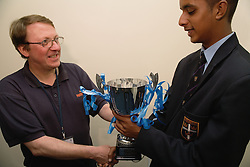 Teacher awarding a trophy to prize winning secondary school student,