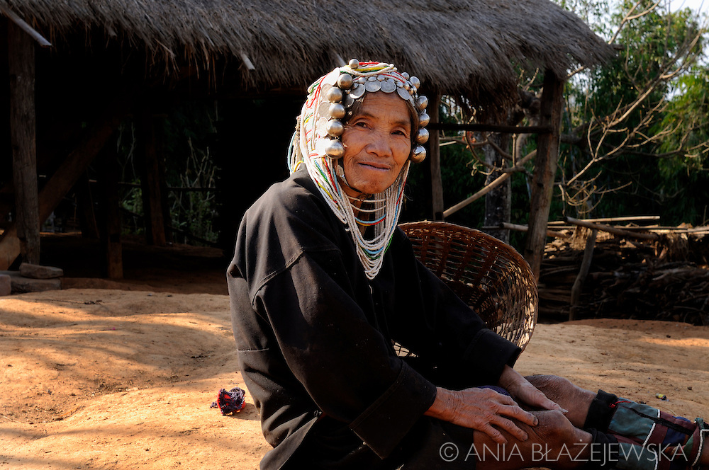 Burma, Myanmar, nearby Kentung.  Woman from Akha hilltribe sitting near her house.