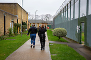 A woman escorted by a female prison officer is escorted to the medical centre inside HMP Downview, Surrey, United Kingdom. HMP Downview is a women's closed category prison for adult sentenced women and convicted and remand female young people located on the outskirts of Banstead in Surrey, England. (Picture credit: © Andy Aitchison)