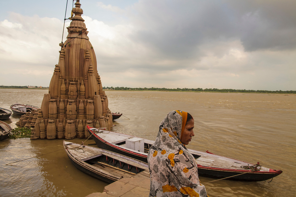 Woman near a sunken temple at Dattatreya Ghat, by the Ganges river, in Varanasi, India.