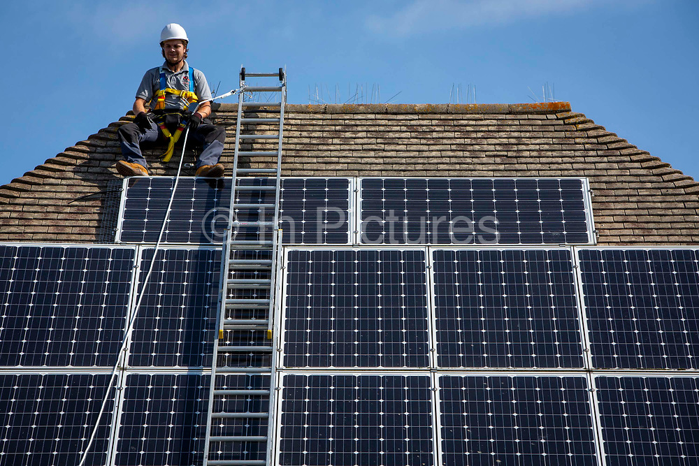 A maintenance person uses a ladder and harnesses to install equipment around a Solar panel array on the roof of a house to stop birds nesting underneath. Folkestone, Kent, United Kingdom.