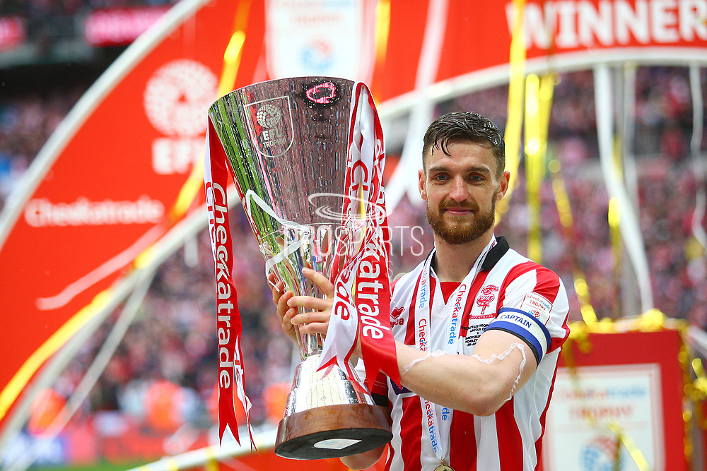 Lincoln City's captain Lincoln City's Luke Waterfall lifts the Checkatrade Trophy during the EFL Trophy Final match between Lincoln City and Shrewsbury Town at Wembley Stadium, London, England on 8 April 2018. Picture by John Potts.