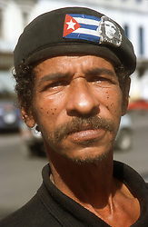 Portrait of man in Havana; Cuba; wearing hat decorated with Cuban flag and image of Che Guevara,