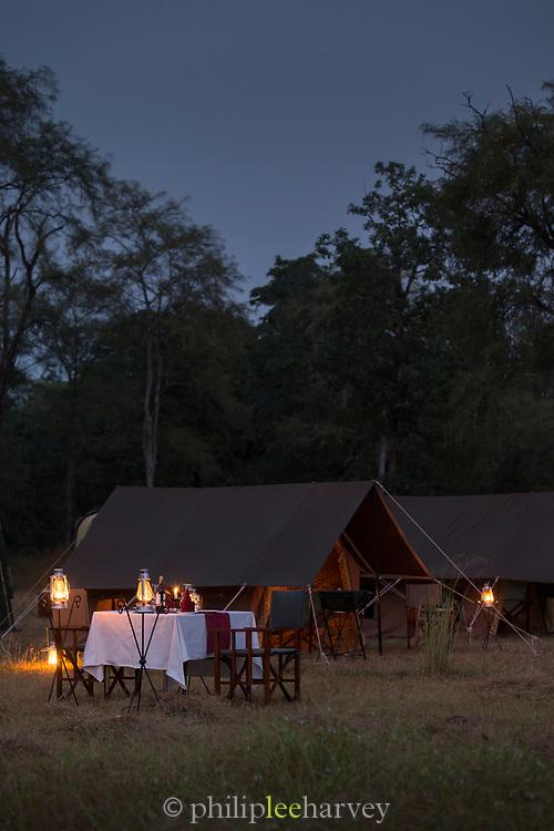 View of illuminated table next to vintage style camping, Rani Pani Safari Lodge, Sohagpur, Madhya Pradesh, India