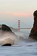 San Francisco Golden Gate Bridge with rocks and sea spray on the foreground.