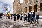 "02 JANUARY 2021 - DES MOINES, IOWA: People gather in front of the Iowa State Capitol. About 30 people marched around the Iowa State Capitol Saturday afternoon to protest the outcome of the November 3 general election in the United States. They are a part of the ""Stop the Steal"" movement which maintains that the election was stolen from Donald Trump by massive voter fraud. There is no evidence supporting their conspiracy theory. This is the 9th week Donald Trump supporters have marched around the Capitol. They've been there every week since the Nov. 3 election. More than 1,000 people showed up the first week, but the crowd has gotten smaller every week.    PHOTO BY JACK KURTZ"