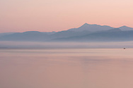 A view of sunrise from Avlaki Beach on Northeast Corfu toward the mountains of Albania.  Corfu, The Ionian Islands, The Greek Islands, Greece, Europe