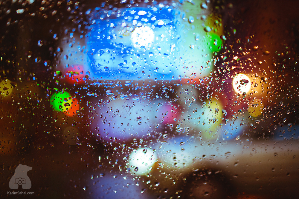 Street lights illuminate water droplets clinging to a window.