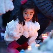 A young girl at the shrine set up around the towns Christmas tree in Sandy Hook after the mass shootings at Sandy Hook Elementary School, Newtown, Connecticut, USA. 16th December 2012. Photo Tim Clayton