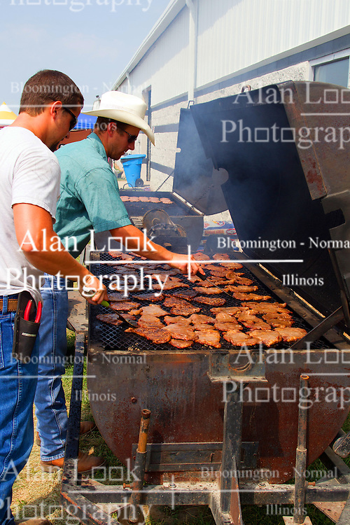 01 August 2014:   McLean County Fair.  Vendors grill hamburgers and pork chops for sandwiches .
