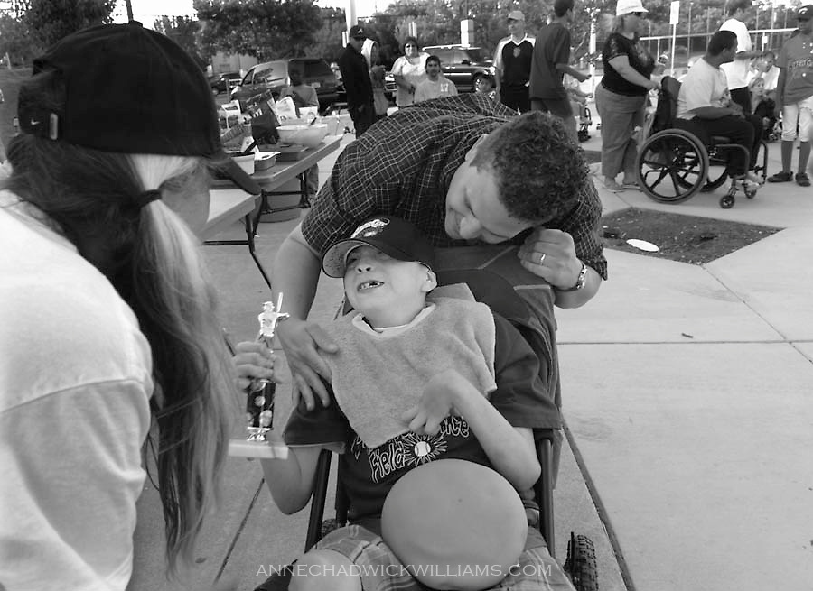 Kevin Kinley gets a trophy after playing in an adaptive baseball game with his mother, Melissa, and her boyfriend at Independence Field on Saturday, June 13, 2009.