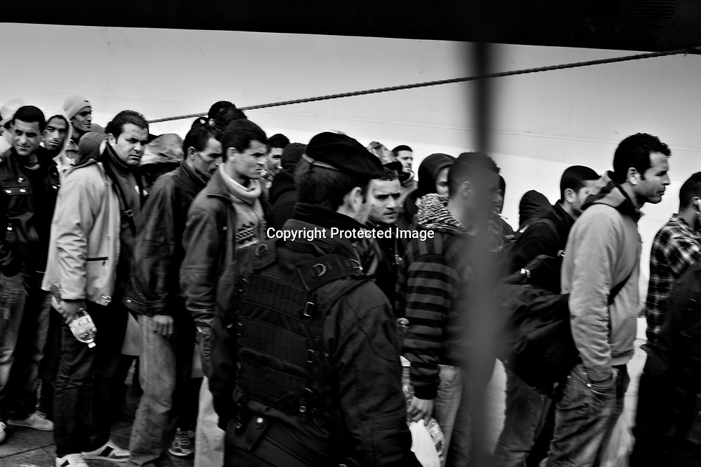 Migrants are being attended on to a ferry that will bring them to a detension center on Sicily.