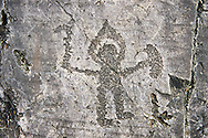 Prehistoric Petroglyph, rock carving, of warrior with a halo type helmet small shield and axe carved by the Camunni people in the iron age between 1000-1600 BC, Seradina I Ronco Felappi Rock 12, Seradina-Bedolina Archaeological Park, Valle Comenica, Lombardy, Italy .<br /> <br /> Visit our PREHISTORY PHOTO COLLECTIONS for more   photos  to download or buy as prints https://funkystock.photoshelter.com/gallery-collection/Prehistoric-Neolithic-Sites-Art-Artefacts-Pictures-Photos/C0000tfxw63zrUT4<br /> If you prefer to buy from our ALAMY PHOTO LIBRARY  Collection visit : https://www.alamy.com/portfolio/paul-williams-funkystock/valcamonica-rock-art.html
