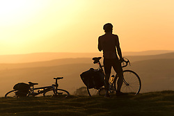 © Licensed to London News Pictures.17/07/2021. Hay Bluff, UK. A cyclist stops at Hay Bluff, near Hay-on-Wye in Powys, Wales to watch the sunset after a very hot sunny day with temperatures reaching as high as 30 C in places. Photo credit: Graham M. Lawrence/LNP