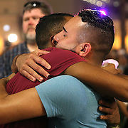 Mourners hug each other during a vigil at the Dr. Phillips Center for the Performing Arts for the victims of a mass shooting at the Pulse nightclub Monday, June 13, 2016, in Orlando, Florida.  A gunman killed dozens of people in a massacre at the crowded gay nightclub in Orlando on Sunday, making it the deadliest mass shooting in modern U.S. history. (Alex Menendez via AP)