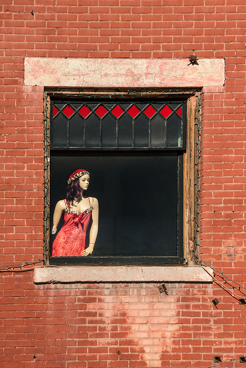 A mannequin with a red cap is on display in a window in the old town house of ill repute in Helper Utah