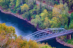 The gorge looking up river at the New River Gorge Bridge in autumn with the fall foliage in partial display.  The smaller steel structure bridge is part of the scenic drive that allows viewing of the New River Gorge Bridge from near the bottom of the gorge.<br /> <br /> HDR (High Dynamic Range) post processing applied.