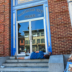 Baltimore, MD - July 26, 2011: A street person sleeps on steps at Recreation Pier at Fells Point in Baltimore. The building was featured as police headquarters for NBCs  Homicide: Life on the Street.