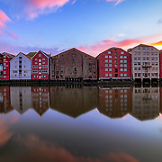 "website: www.azinasutiphotography.com                               At Nidelva's outlet there have been seaside stalls, breweries and warehouses all the way from the oldest times. Here the towners traded with goods from far and near.<br /> <br /> At the time of King Sverres, the bridges were also used as defense works. Towards the river, screens and times were built. From here you could throw stones on the enemy. In Magnus Lagabøte's city council of 1276, it is stated that the swallow, a passageway outside the bridges, should not be wider than three ales; further that between the brews should be ""droplet"" distance. The brewery that is still preserved is located on both sides of Nidelva - in Kjøpmannsgata, in Bakklandet, in Fjordgata and Sandgata. The oldest preserved breweries are from the mid-18th century."