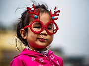 24 DECEMBER 2017 - HANOI, VIETNAM: A child wearing Christmas themed antler glasses frames at a holiday street fair in the old quarter of Hanoi. The commercial and gift giving aspect of Christmas is widely celebrated in Vietnam and Vietnam's 5+ million Catholics celebrate the religious aspects of Christmas.     PHOTO BY JACK KURTZ