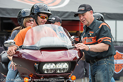 Kurt Allison who hails from West Bend, WI and works at the Menominee Falls HD plant as a machine mechanic helps Shawn and Kim Evenson of Plymouth, NH before they test ride a 2017 Road Glide Ultra that particularly interests them. They are attracted to its new Milwaukee-8 engine (despite having 1993, 2002 and 2005 HD's home in their garage). Harley-Davidson test ride area that was recently moved right into Weirs Beach for the 2017 Laconia Motorcycle Week, New Hampshire, USA. Sunday June 18, 2017. Photography ©2017 Michael Lichter.