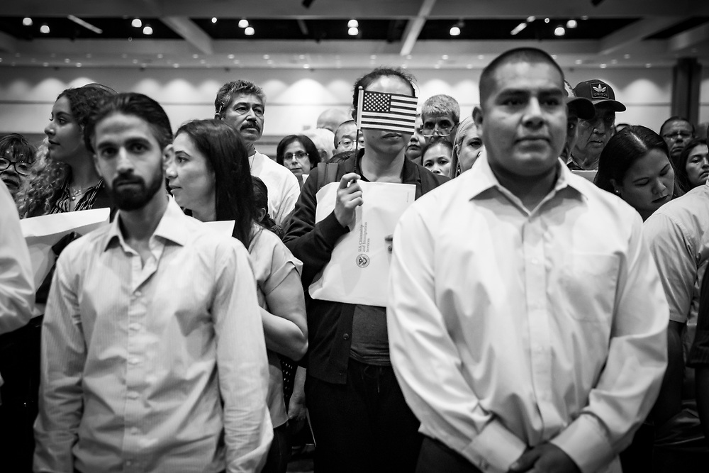 Naturalized citizens wait their turn to exit the ceremony and receive their official certificate of citizenship.