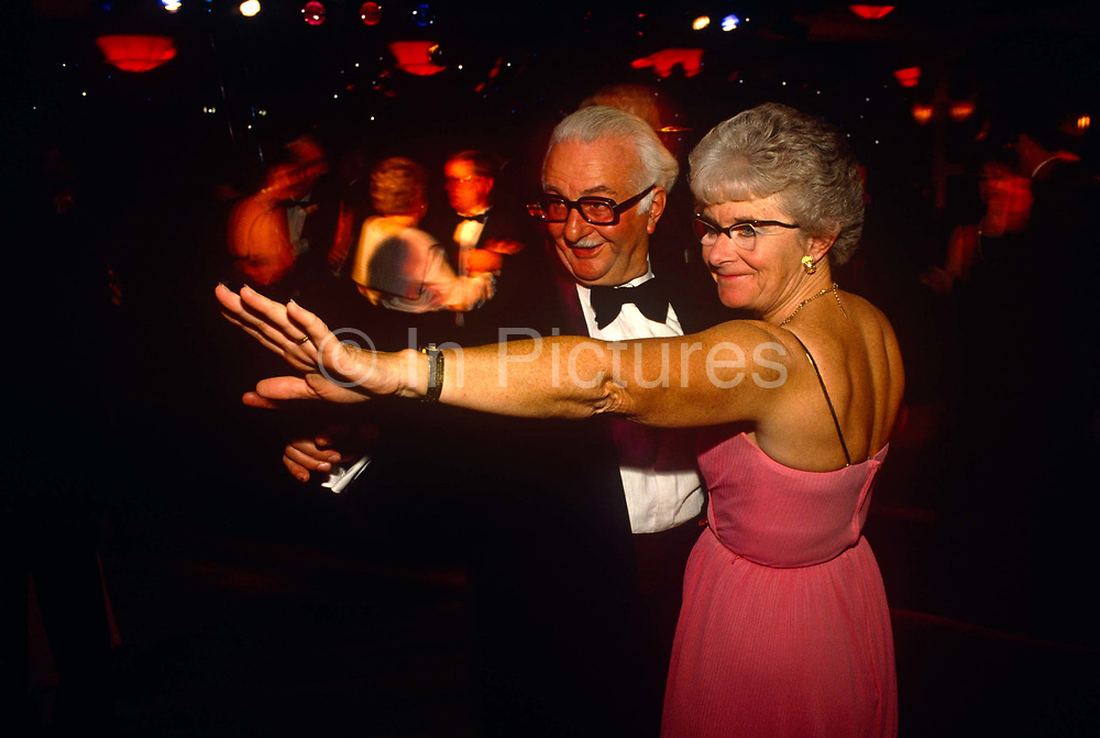 Both wearing slightly ridiculous pairs of glasses, two delegates dance on the floor at the annual Party Conference of 1990 at Blackpool during the premiership of Prime Minister John Major. The dance they are attempting allows them to somehow stretch out their arms to make a theatrical point. The lady is wearing a bare-backed dress with old-fashioned spectacles while her partner wears a formal dinner suit including a black bow tie and with thick-rimmed glasses. They are at this evening event to help raise funds for Britain's Conservative Party under the leadership of the then PM Major who had just taken over the running of the country from the deposed Margaret Thatcher earlier that year.