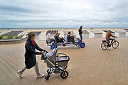 Belgie, Oostende, 6-9-2019 Aan het strand langs de Noordzee van deze mondaine badplaats in vlaanderen. Toeristen op een skelter, vrouw met kinderwagen en man op fiets op de boulevard .Foto: Flip Franssen