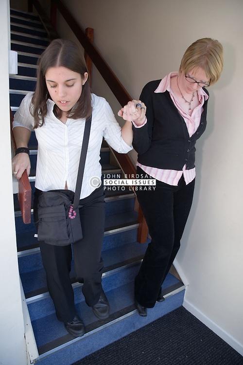 Young woman being help down the stairs by a colleague at work,